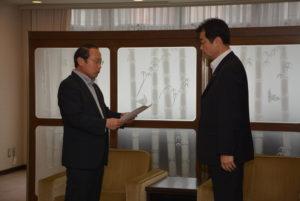 「新たな観光資源の創出」について特別委員会の報告書を永田雅紀議長(右)に提出する若林新三委員長(左)